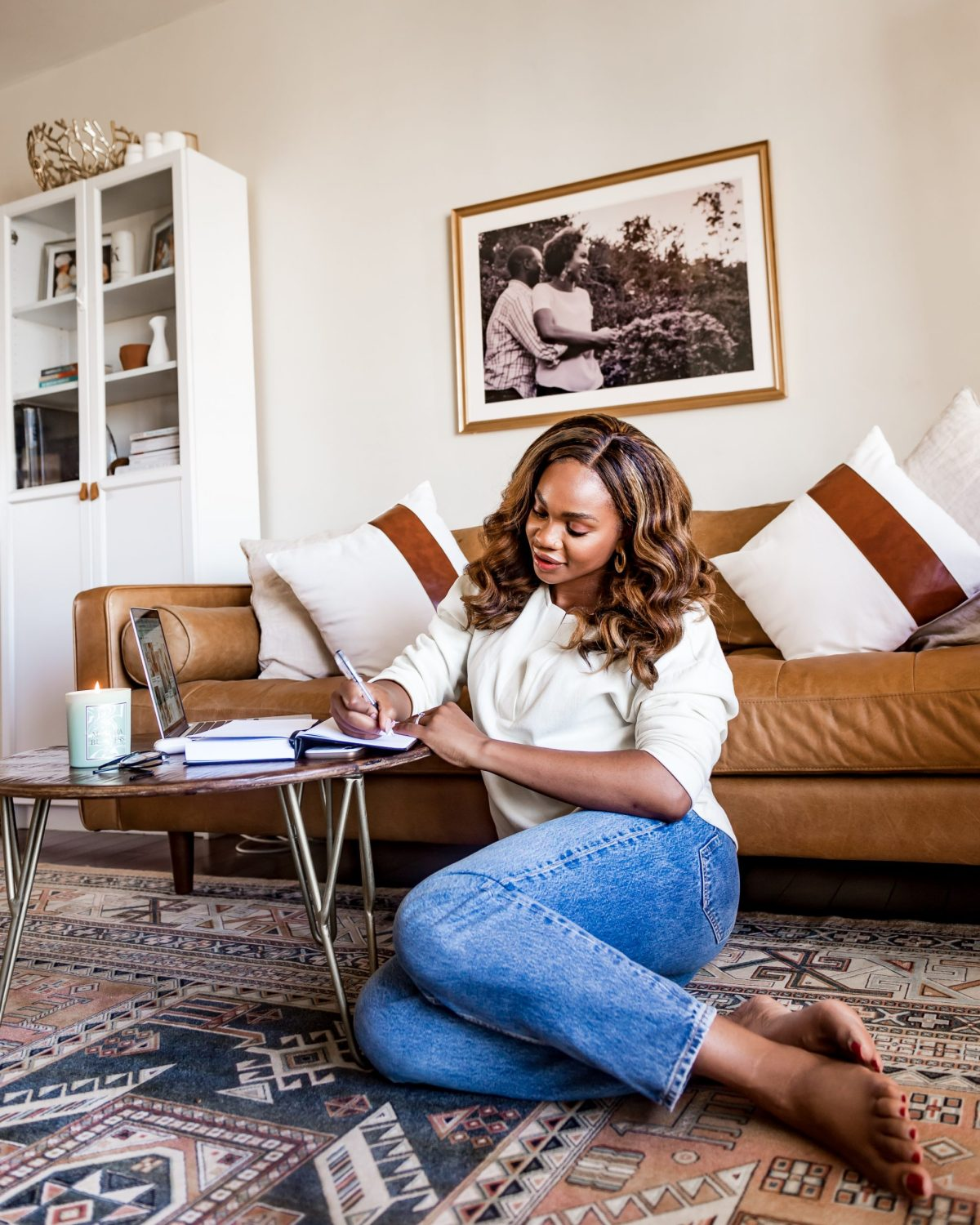 Ijeoma Kola sitting on living room floor and writing in journal - 2021 resolutions blog