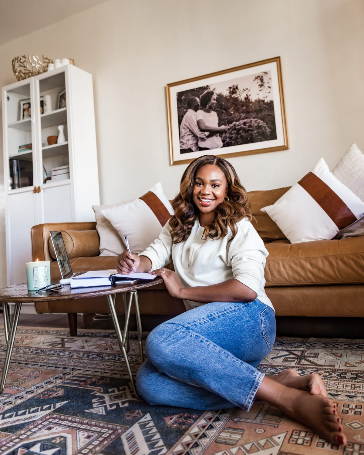Ijeoma Kola sitting on living room floor with laptop and journal