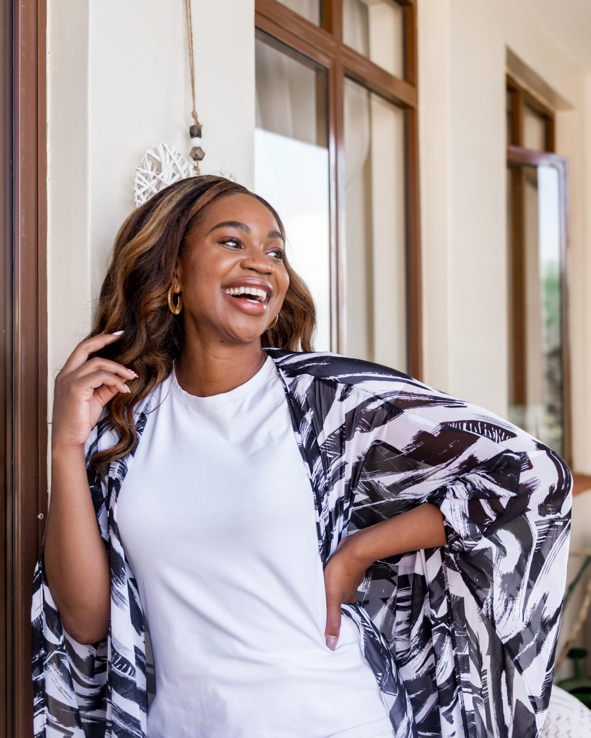 Ijeoma Kola laughing in white outfit and black and white kimono | Black owned brands