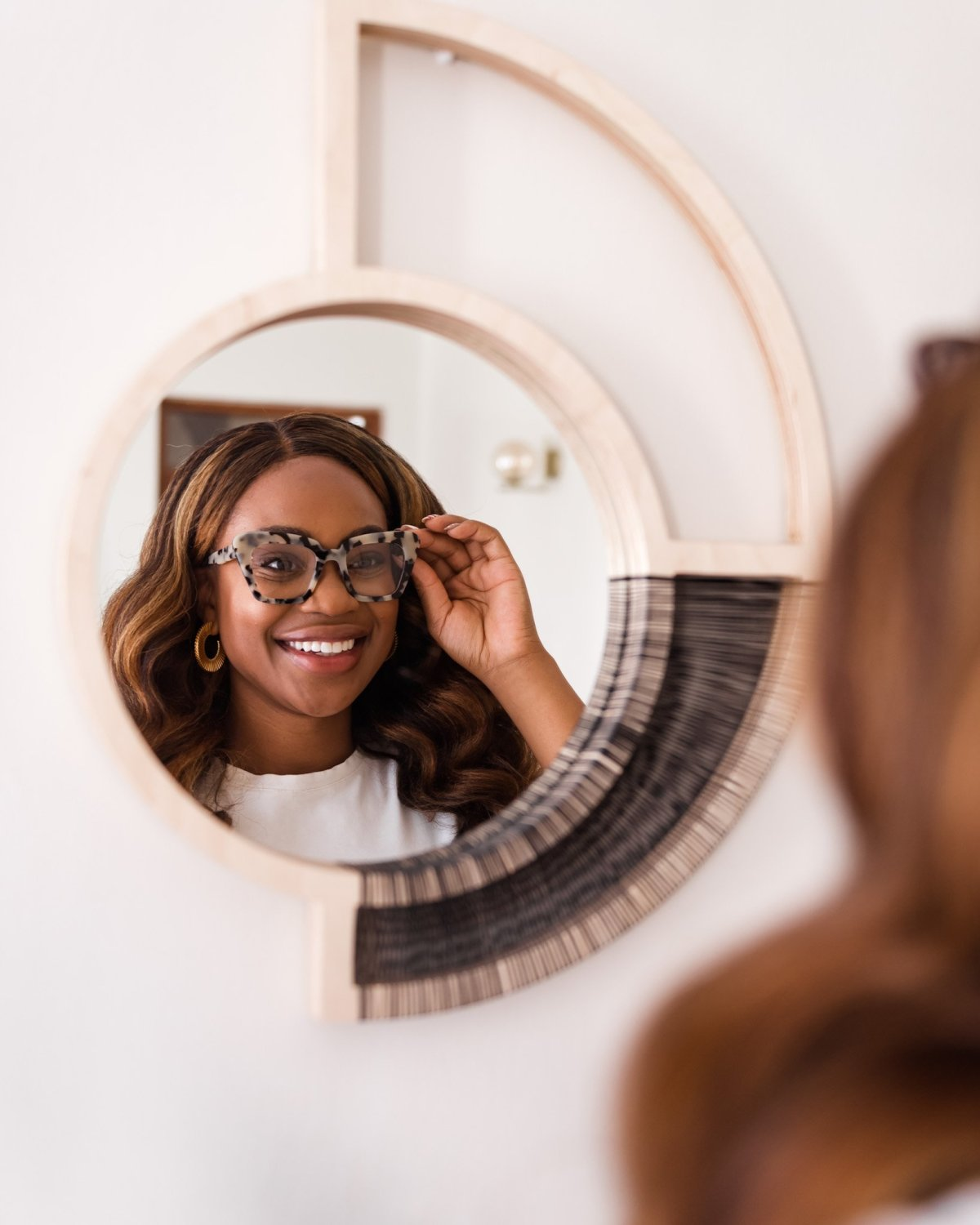 Ijeoma Kola smiling into round wall mirror while holding eyeglasses