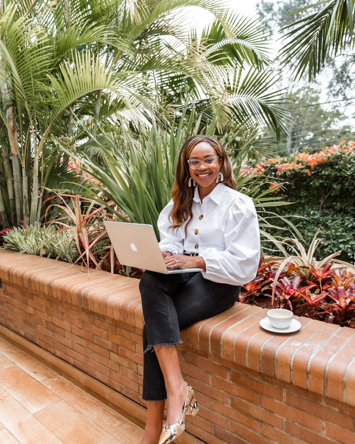 Ijeoma Kola sitting outdoors and smiling with computer on lap and cup of tea next to her