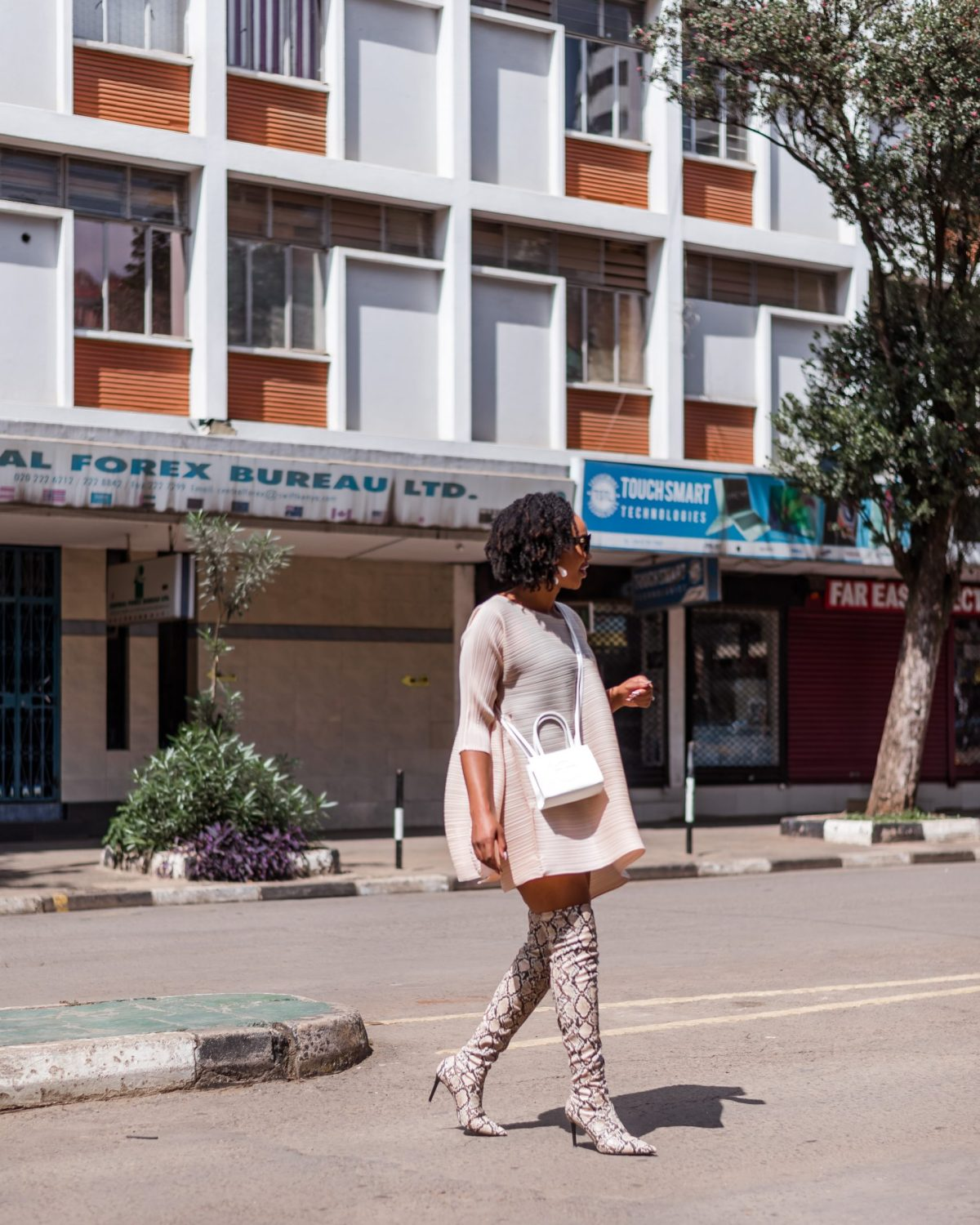 Ijeoma Kola crossing the streets of Nairobi wearing cream mid-sleeve dress, white shoulder sling bag and snake skin thigh high boots - Blog on how to make extra money
