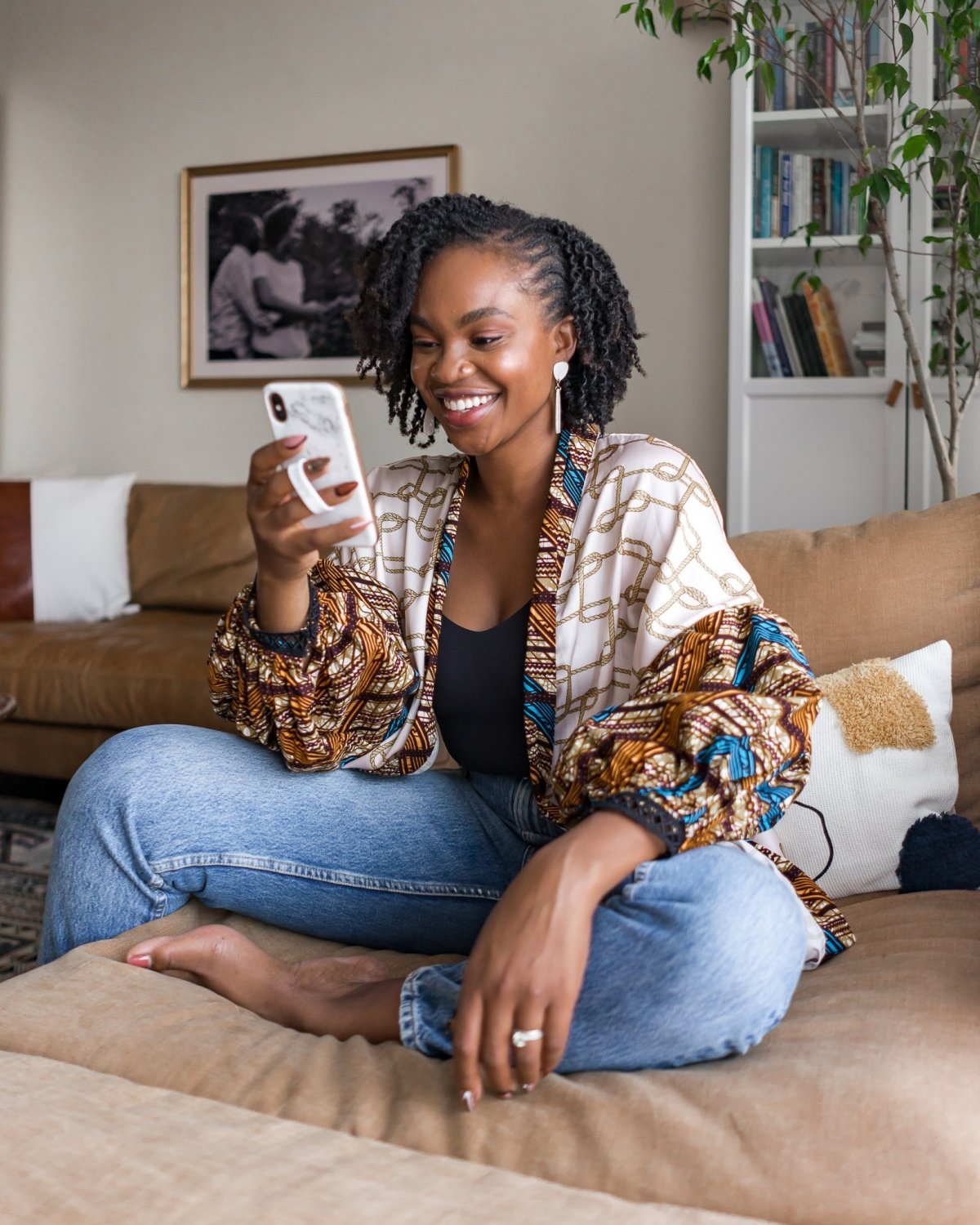 Ijeoma Kola sitting barefoot on couch and smiling while scrolling through her phone - Ijeoma Kola monthly Q&A January 2021