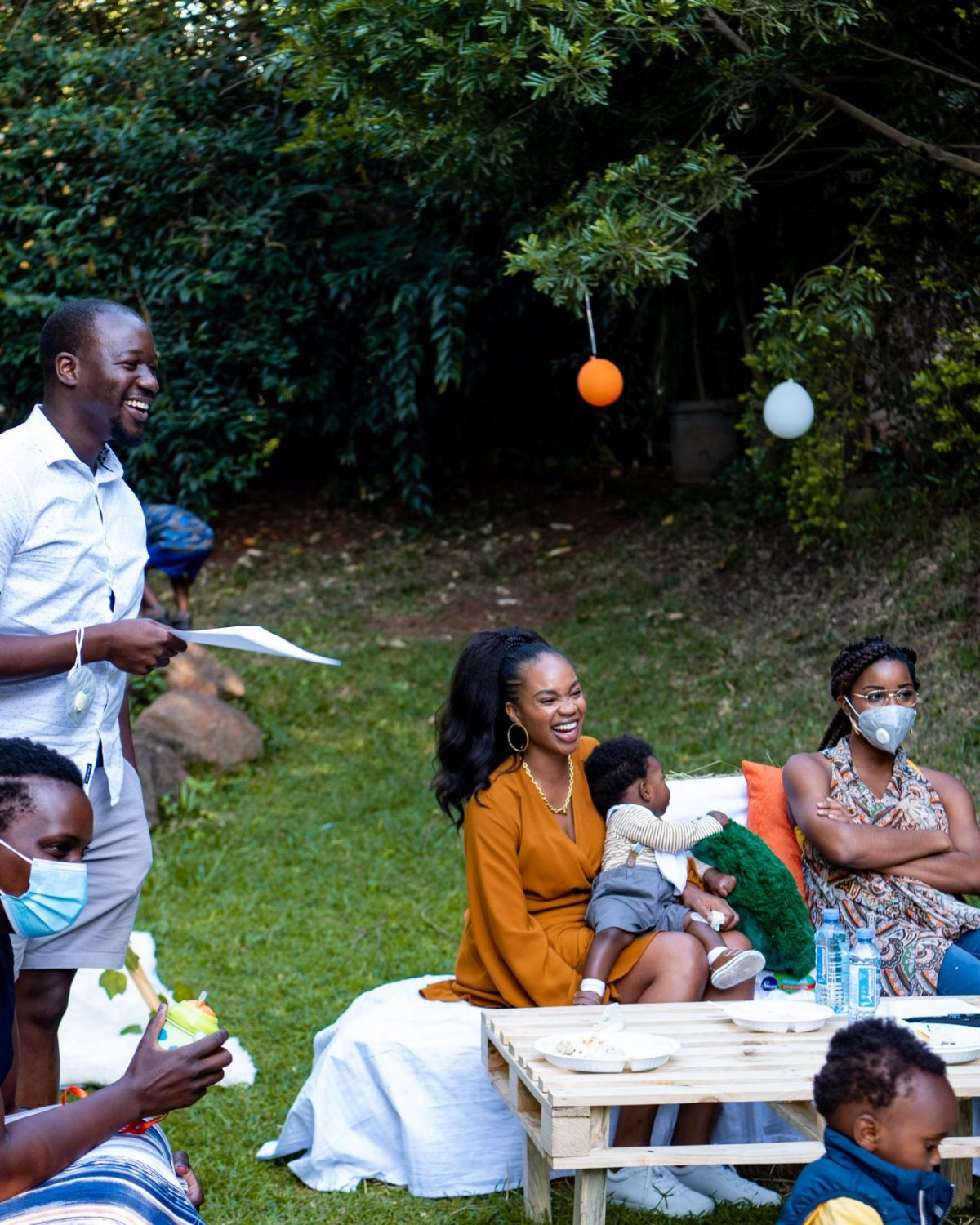 Ijeoma Kola laughing at picnic with baby on lap surrounded by family and friends