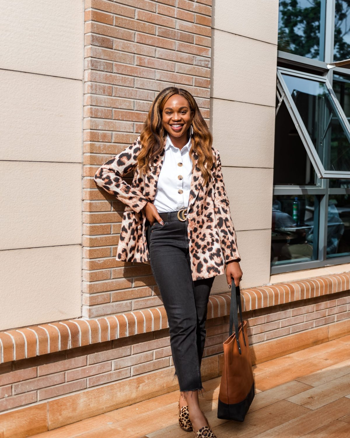 Full outfit shot of Ijeoma Kola posing outside with hand on hip wearing animal print blazer, white shirt, black pants and shoes - How Black Owned Businesses Can Optimize Black History Month