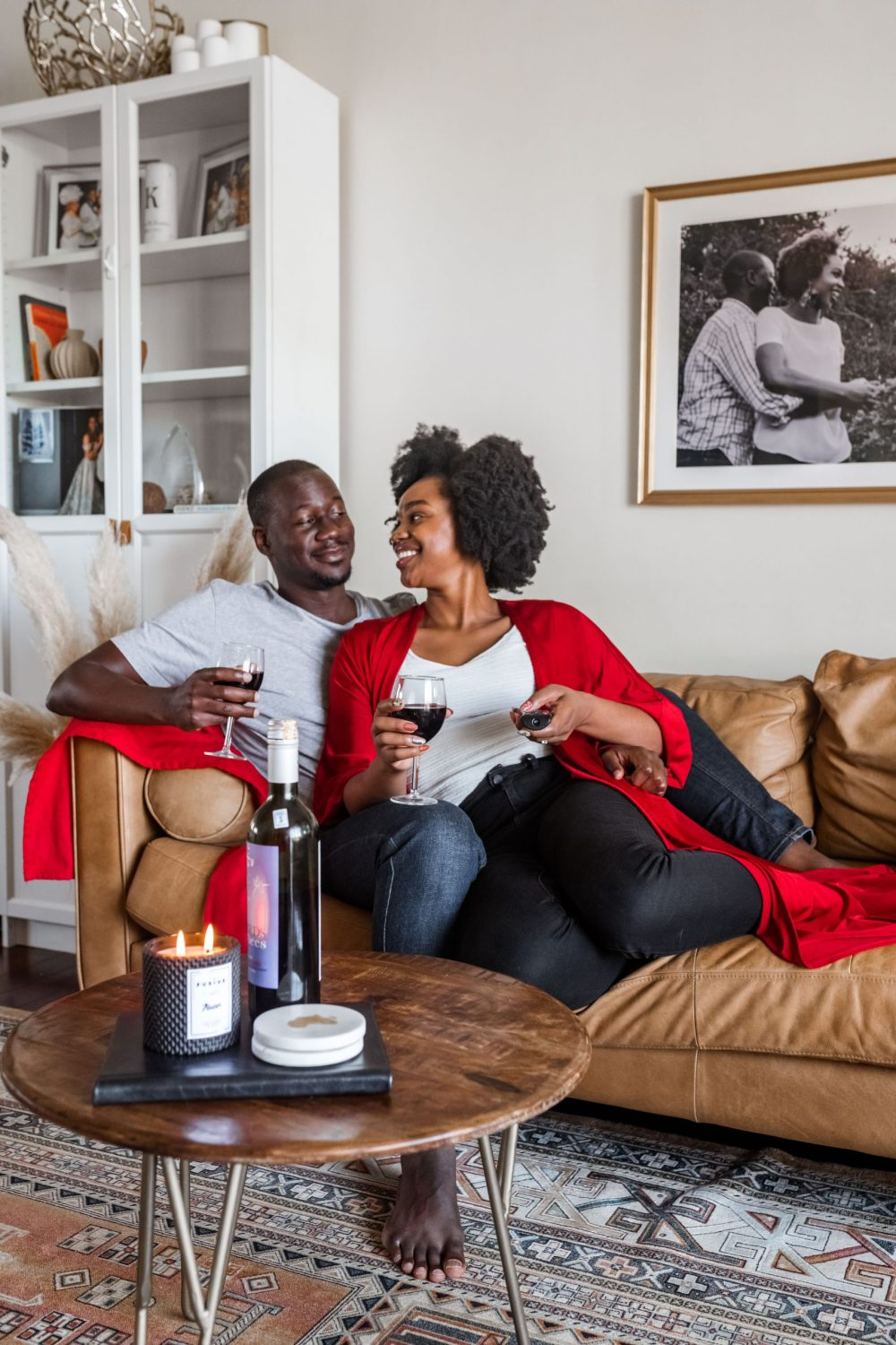Ijeoma and Jonathan Kola chilling on and smiling at each other on couch with wine on Valentine's Day - Stay at Home Valentine's Day Ideas