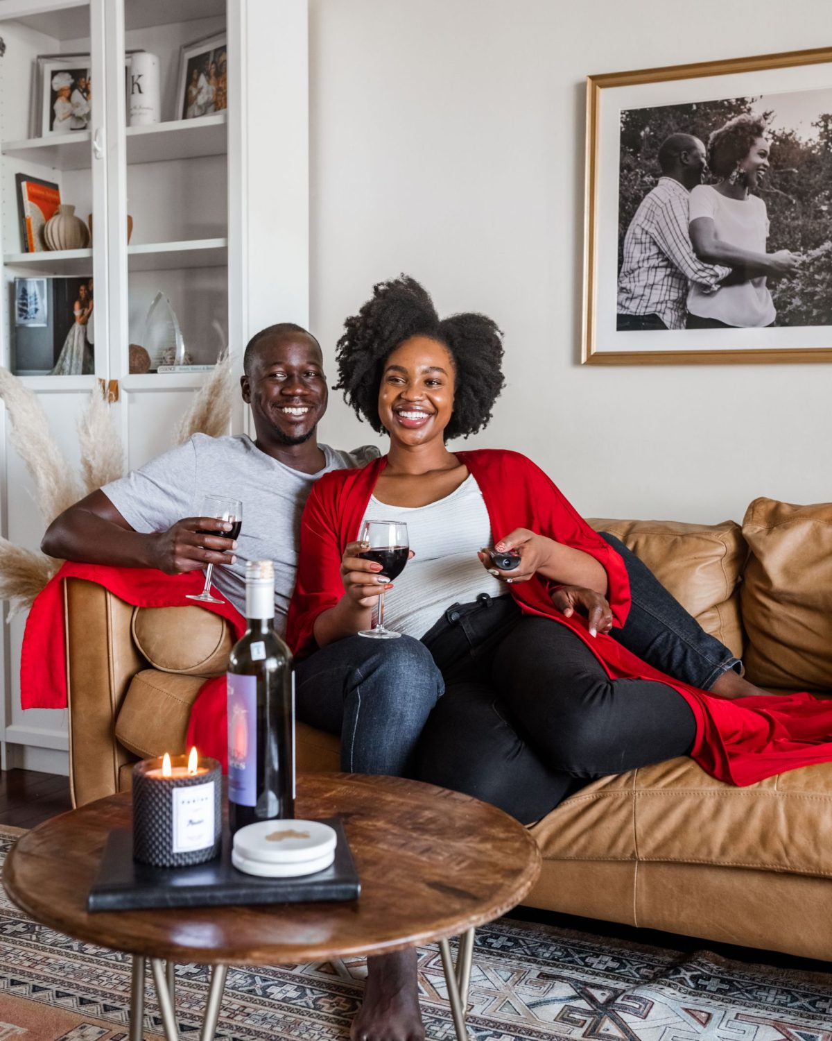 Ijeoma and Jonathan Kola cuddling on couch with wine on Valentine's Day - Stay at Home Valentine's Day Ideas