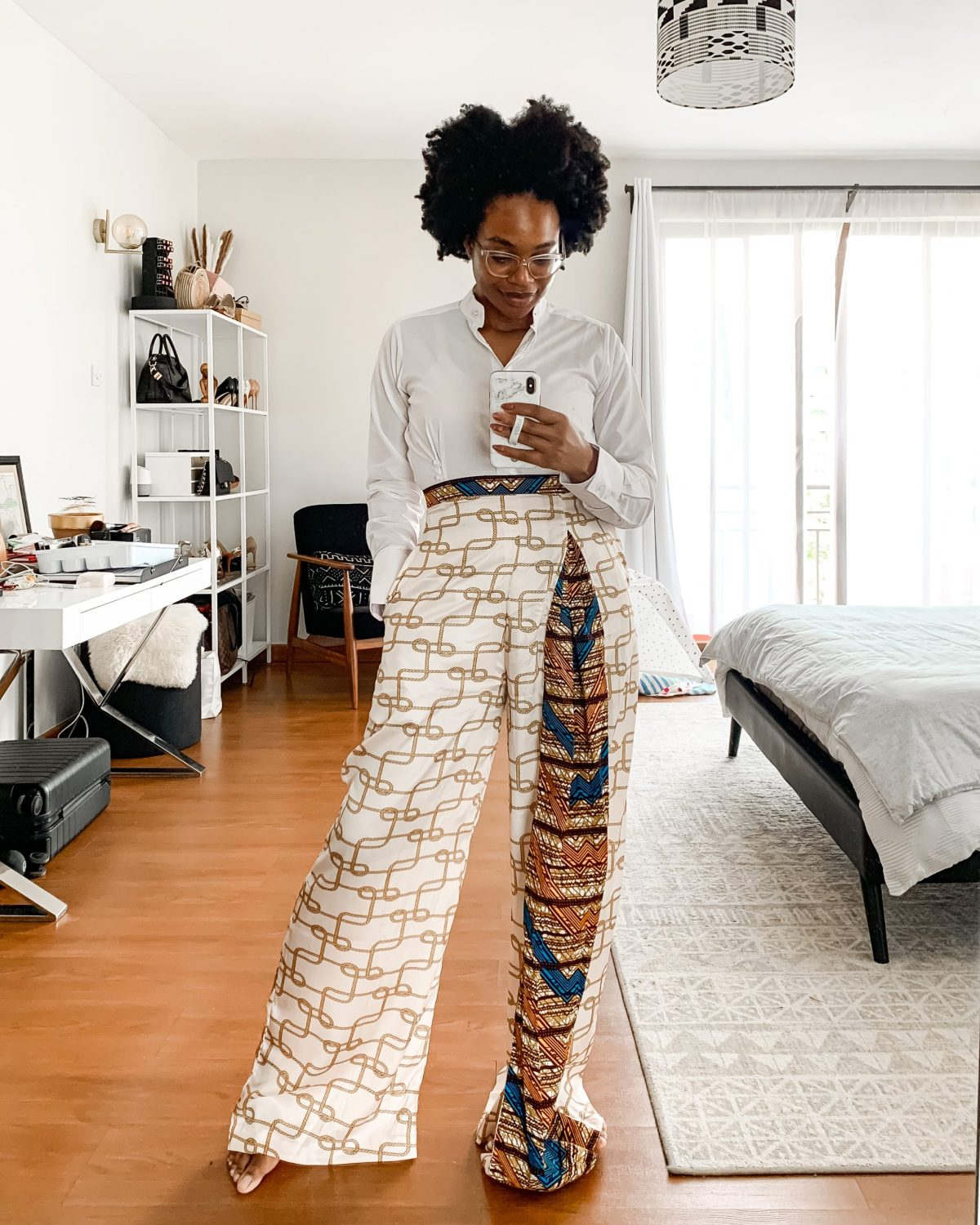 Ijeoma Kola posing in print pants and white shirt taking mirror selfie - Financial lessons blog