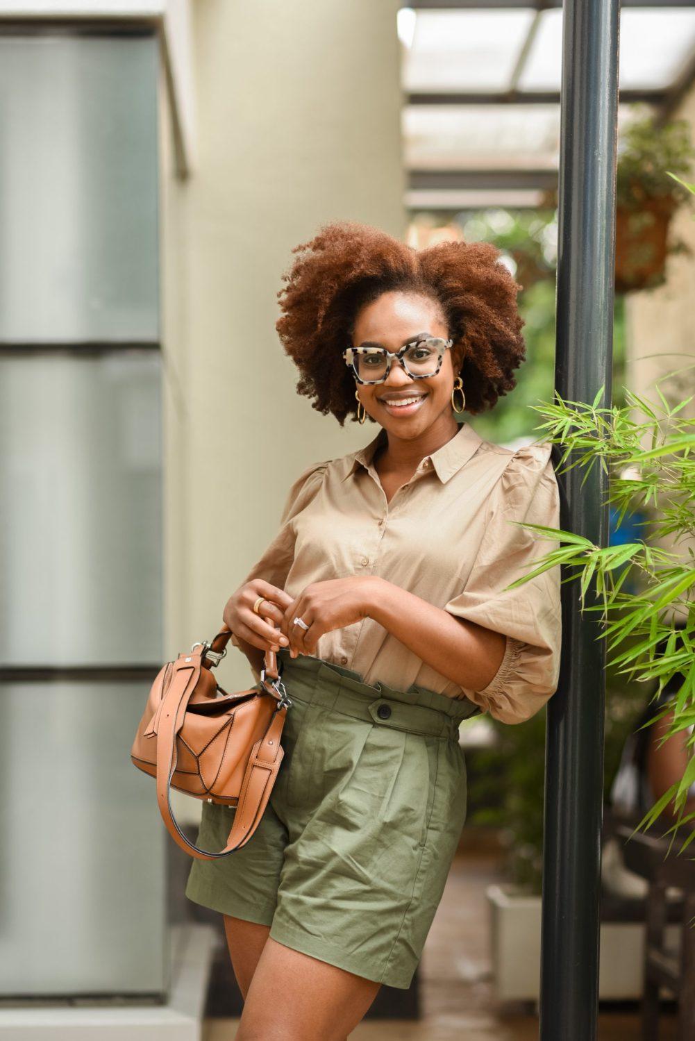 Ijeoma Kola posing in beige shirt and khaki shorts with brown handbag