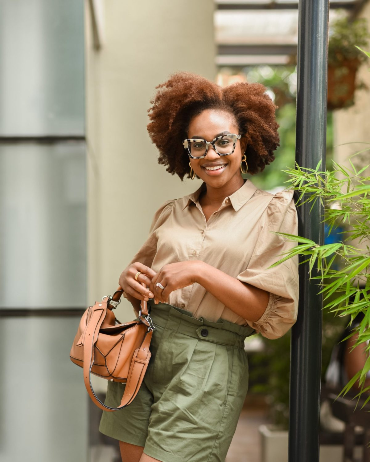 Ijeoma Kola posing in beige shirt and khaki shorts with brown handbag