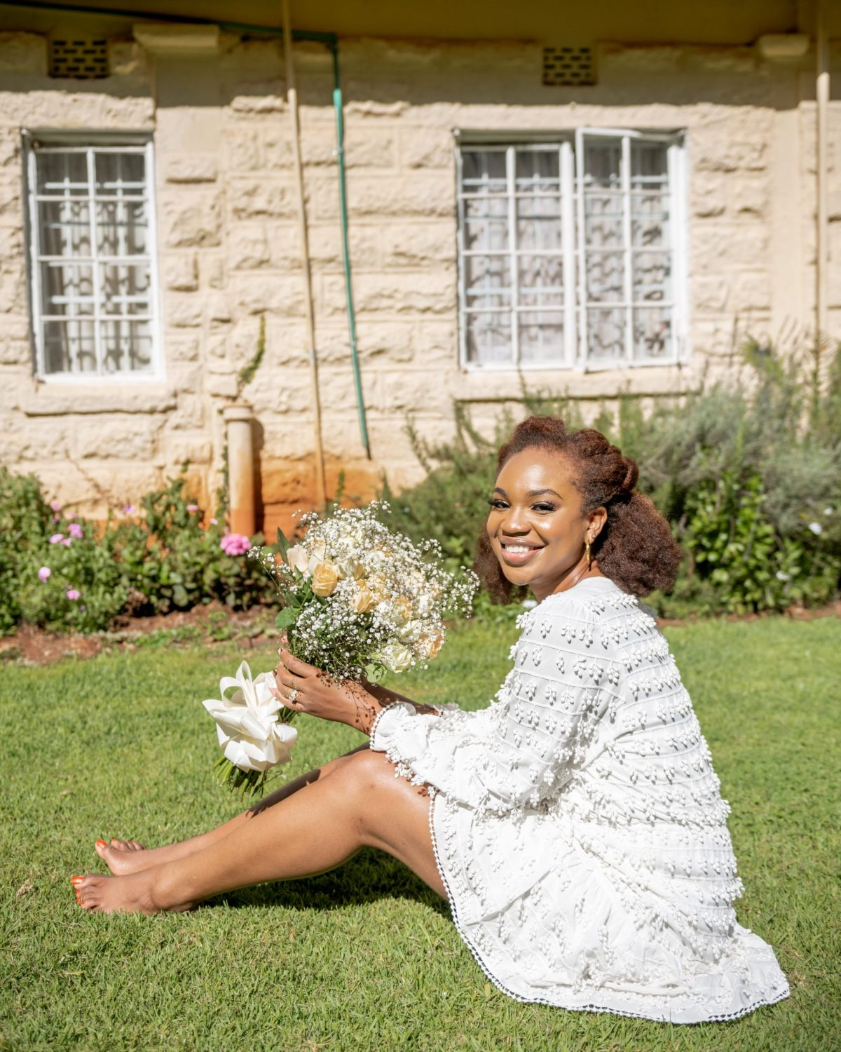 Ijeoma Kola sitting on grass in a white dress in front of a house