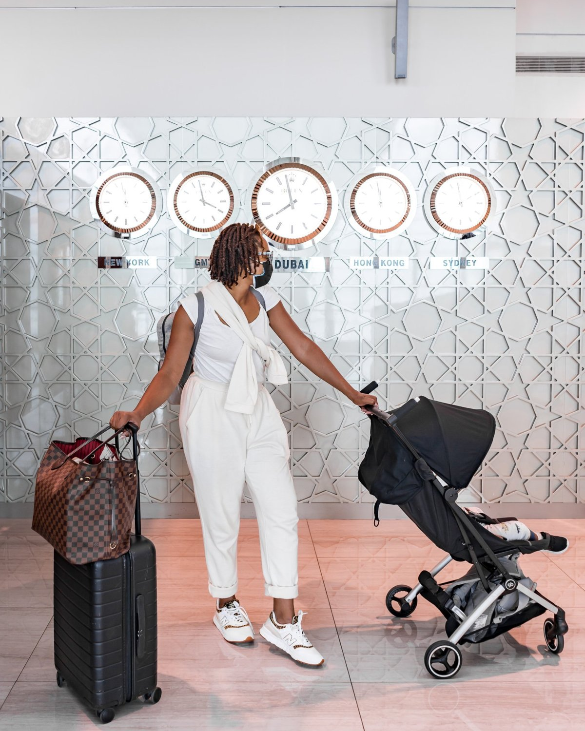Ijeoma Kola at Dubai Airport with Away Carry On, Louis Vuitton Neverfull, and GB PockIt Stroller