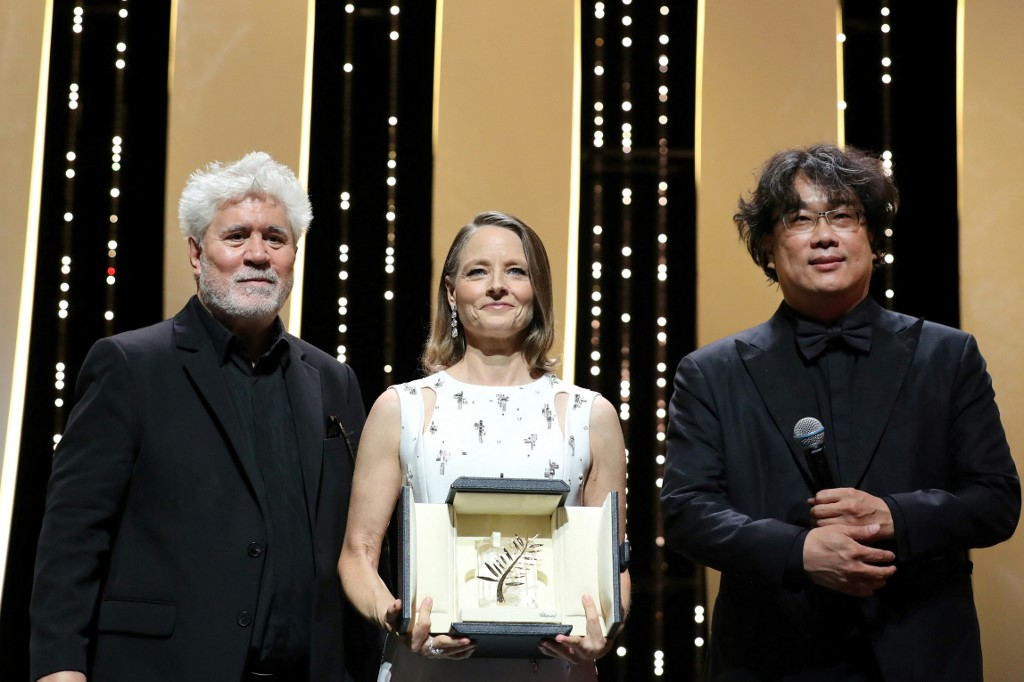 US actress and director Jodie Foster (C) poses on stage with Spanish director Pedro Almodovar (L) and South Korean director Bong Joon-Ho after she received a Palme d'Or Life Achievement Award during the opening ceremony of the 74th edition of the Cannes Film Festival in Cannes, southern France, on July 6, 2021. (Photo by Valery HACHE / AFP)