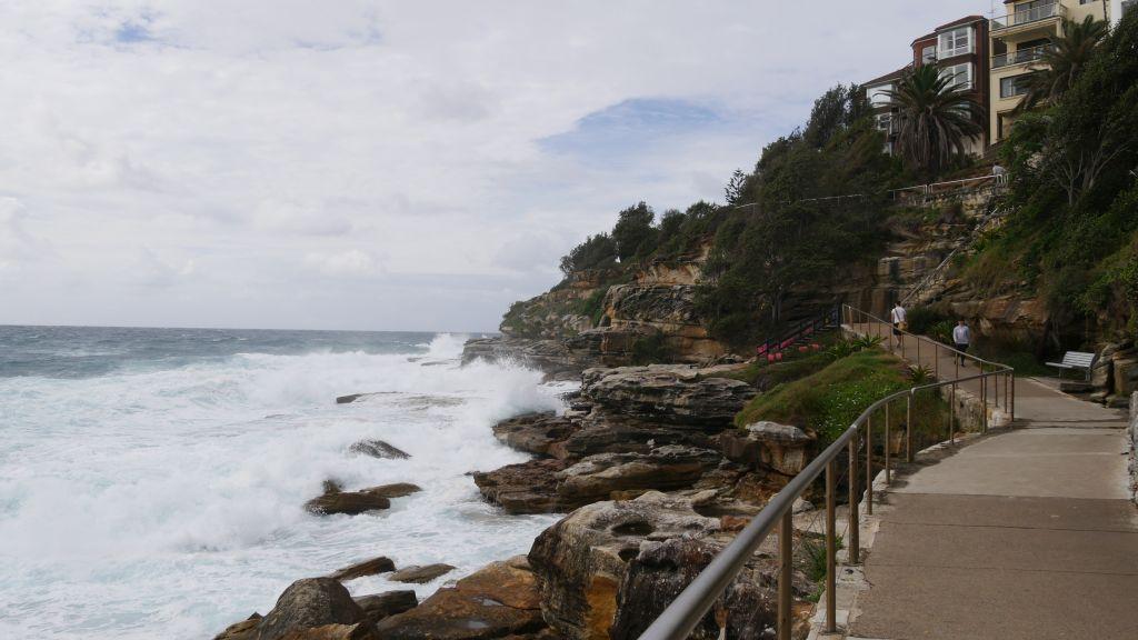 Stenen wandelpad met aan de linkerkant rotsen en de zee