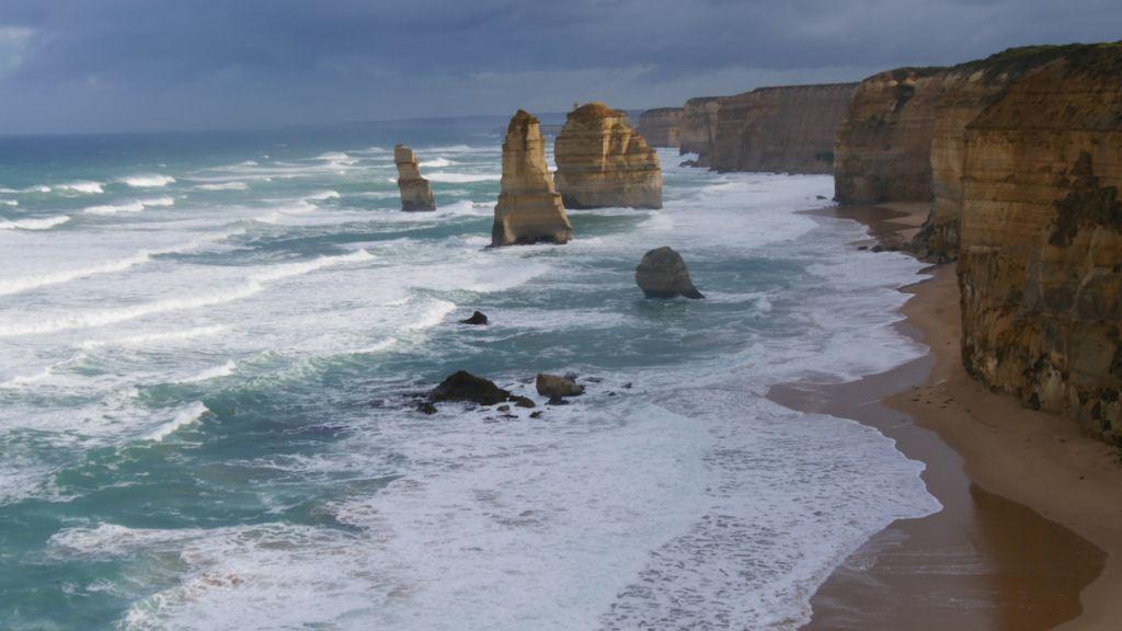 Foto met de 12 Apostels langs de Great Ocean Road, blauwe zee, blauwe luct en rotsen die in het water staan en uitsteken