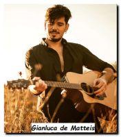 Nuovo tronista di Uomini e donne Gianluca de Matteis mentre suona la chitarra in un campo di grano.