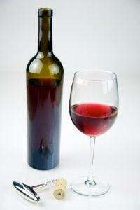 Glass of Red Wine with a bottle of Red Wine shot on a white background.