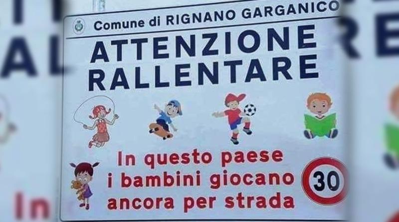 """Un cartello stradale che fa notizia: in un piccolo paese del Sud si legge """"Attenzione rallentare, in questo paese i bambini giocano ancora per strada"""""""