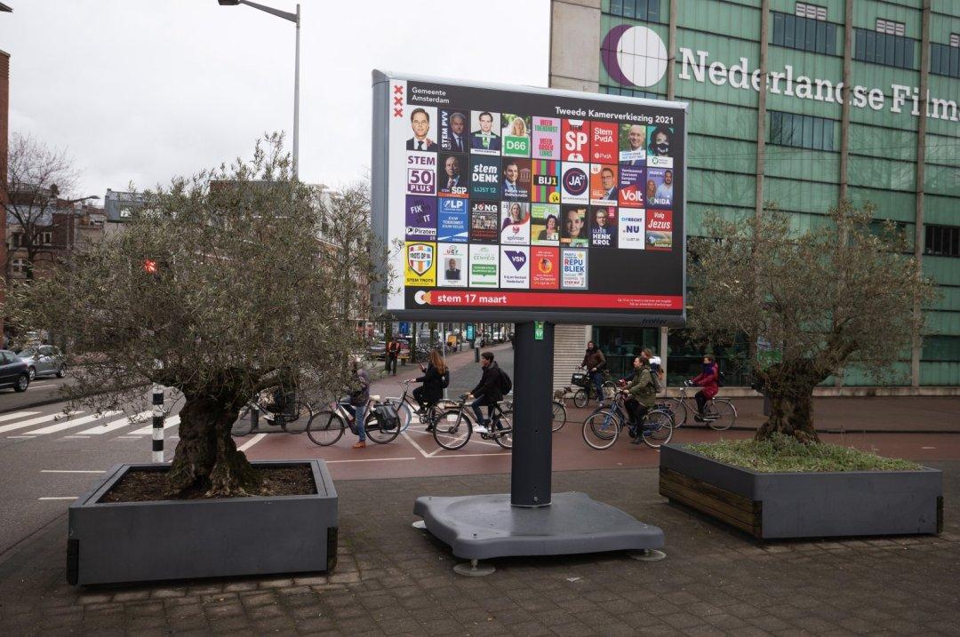 9 Mart 2021 Salı günü Amsterdam, Hollanda'da bir reklam panosundaki Hollanda siyasi parti seçim kampanyası afişlerinin yakınında bir yol geçişinde bisikletliler. (Getty Images)