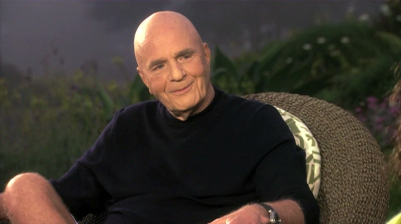 Dr Wayne Dyer sitting in a chair and smiling, bald wearing a black shirt