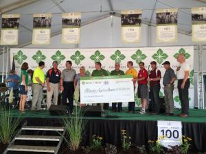 Susan Wall on stage at the Farm Progress Show at Decatur Illinois in Sept. 2015 accepting IAW's part of a $100,000 prize from Farm Credit for being chosen as one of the ten top groups of Illinois who serves agriculture.