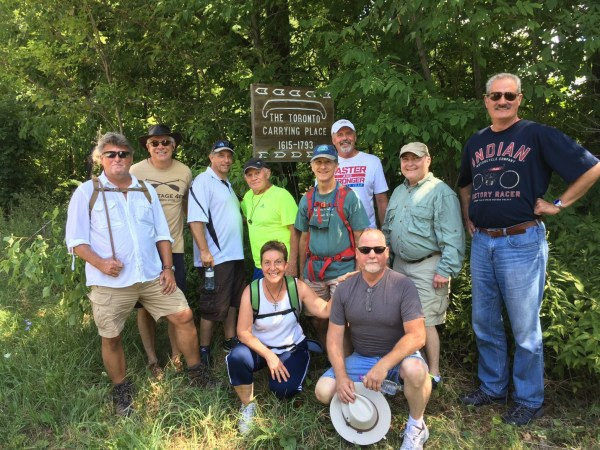 La Salle II veterans pause at a sign identifying the historic voyageur portage route. They include (standing from left) Keith Gorse, Bob Kulick, Gary Braun, Terry Cox, George Lesieutre, Sam Hess, Chuck Campbell and Marc Lieberman and (kneeling) Cathy Palmer and Randy Foster. Palmer was a member of the liaison team.