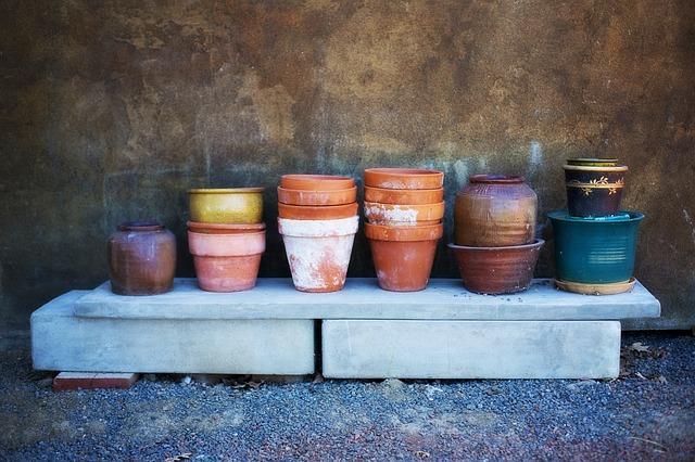 Un vaso di terracotta tra vasi di ferro