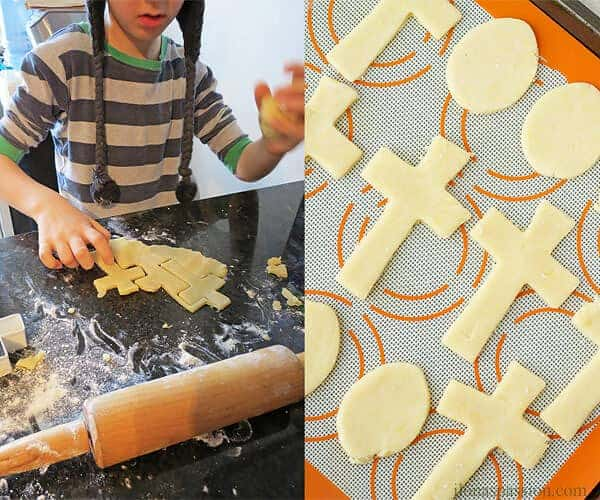 A boy makeing cross sugar cookies on the left and ready to be backed cut out Easter cookies on the right.