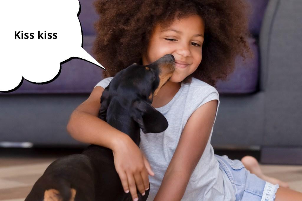 Girl sitting on the floor cuddling a dachshund