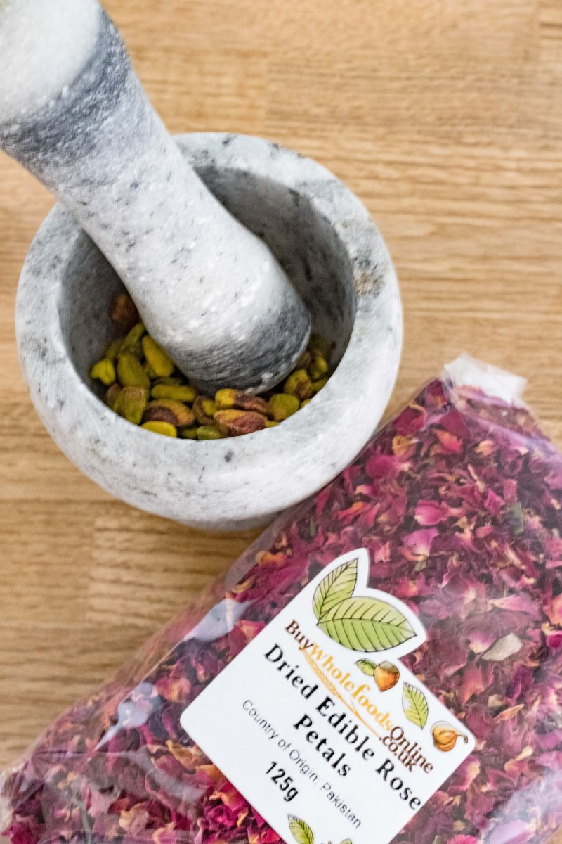 Mortar and Pestle with Crushed Pistachios and Dried Edible Rose Petals by Buy Whole Foods Online
