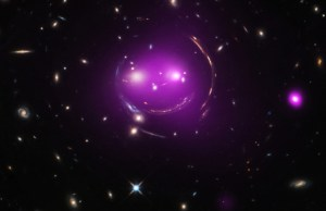 """Astronomers think that in the future the """"Cheshire Cat"""" group will become what is known as a fossil group, a gathering of galaxies that contains one giant elliptical galaxy and other much smaller, fainter ones. Today, researchers know each """"eye"""" galaxy is the brightest member of its own group of galaxies and these two groups are racing toward one another at over 300,000 miles per hour. Data from Chandra (purple), which has been combined with optical data from Hubble, show hot gas that has been heated to millions of degrees, which is evidence that the galaxy groups are slamming into one another. Chandra's X-ray data also reveal that the left """"eye"""" of the Cheshire Cat group contains an actively feeding supermassive black hole at the center of the galaxy."""