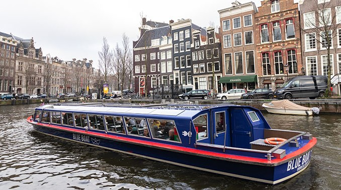 Amsterdam met rondvaartboot in de gracht en grachtenpanden