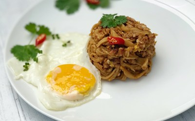 Thai style egg noodles stir-fry served with fried egg