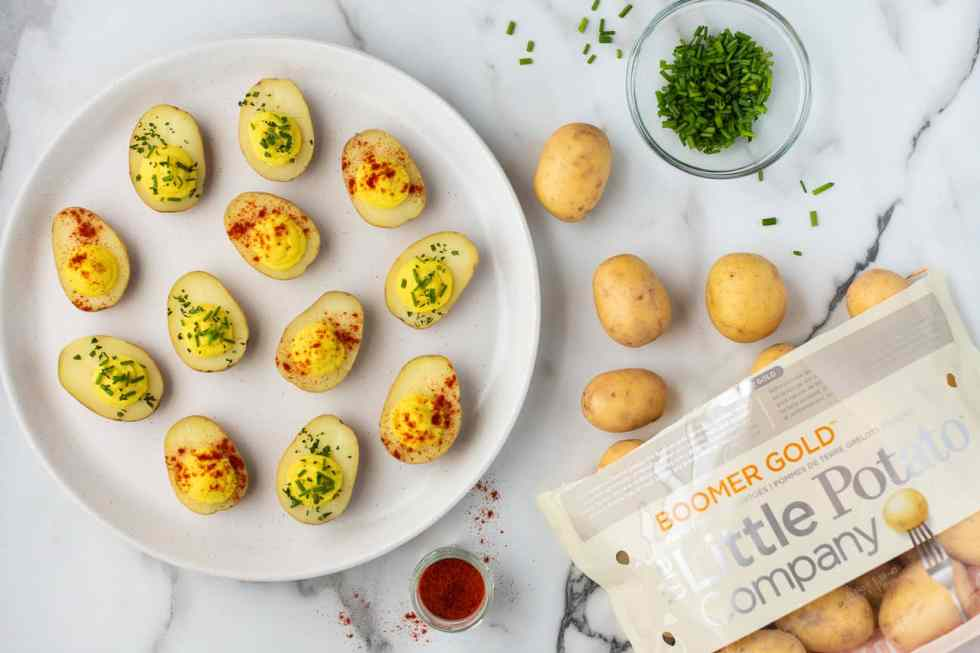 Vegan deviled egg potatoes garnished with paprika and fresh chives.