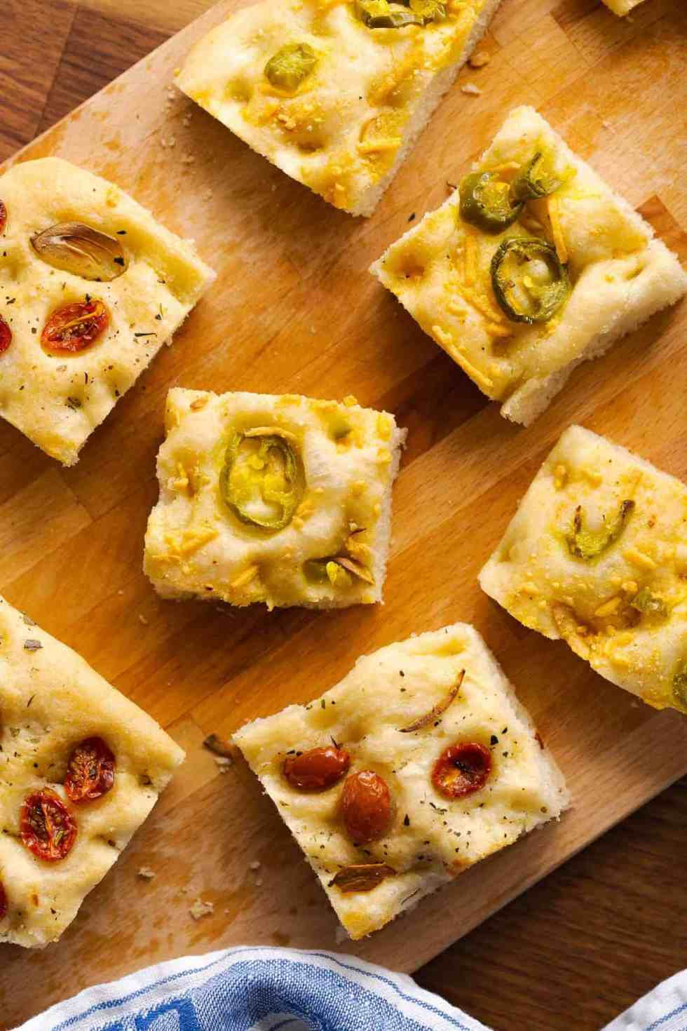 Square slices of jalapeno cheese focacccia and tomato herb focaccia on a wood cutting board.