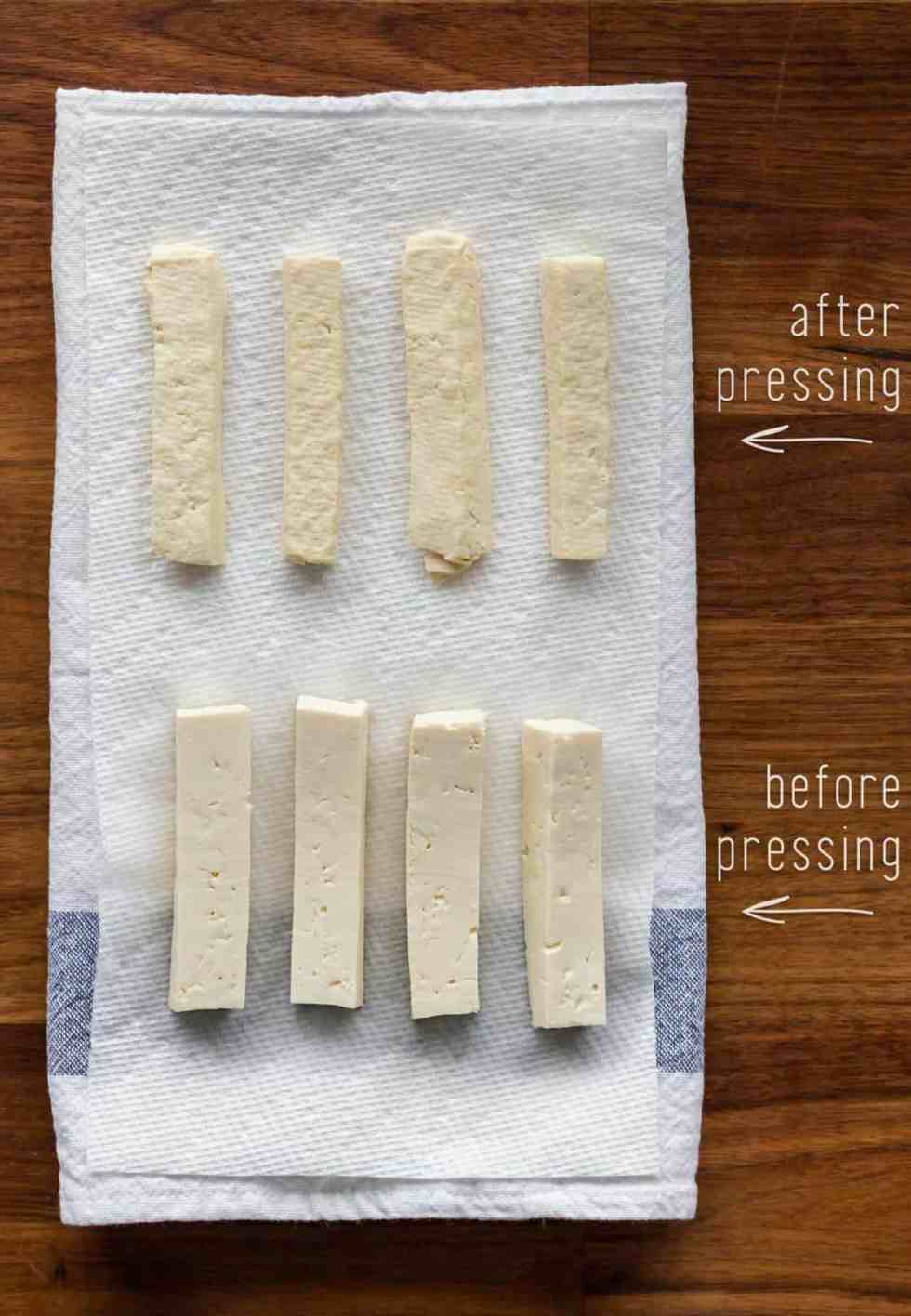 Medium-firm tofu cut into rectangles laying on a kitchen towel. Top row shows pressed tofu (dry to the touch and barely beginning to crumble). Bottom row shows silky, unpressed medium-firm tofu.