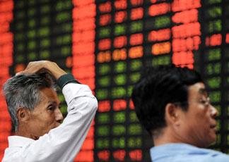 Investitori cinesi preoccupati di fronte a un tabellone con i dati della Borsa di Shanghai (Afp)