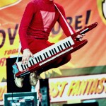 Member of the group 2 Skinnee J's Jumping while playing keyboard.