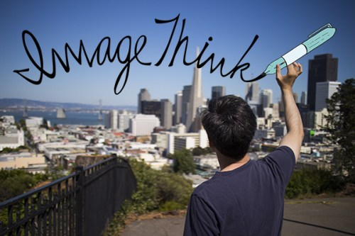 ImageThink graphic recording company office opens up in San Francisco. Photo of the back of Senior Graphic Recorder James Lake lifting up & cartoon marker & writing the ImageThink logo over the skyline of san francisco. He's on a tall hill in a park, the city & water in the distance.
