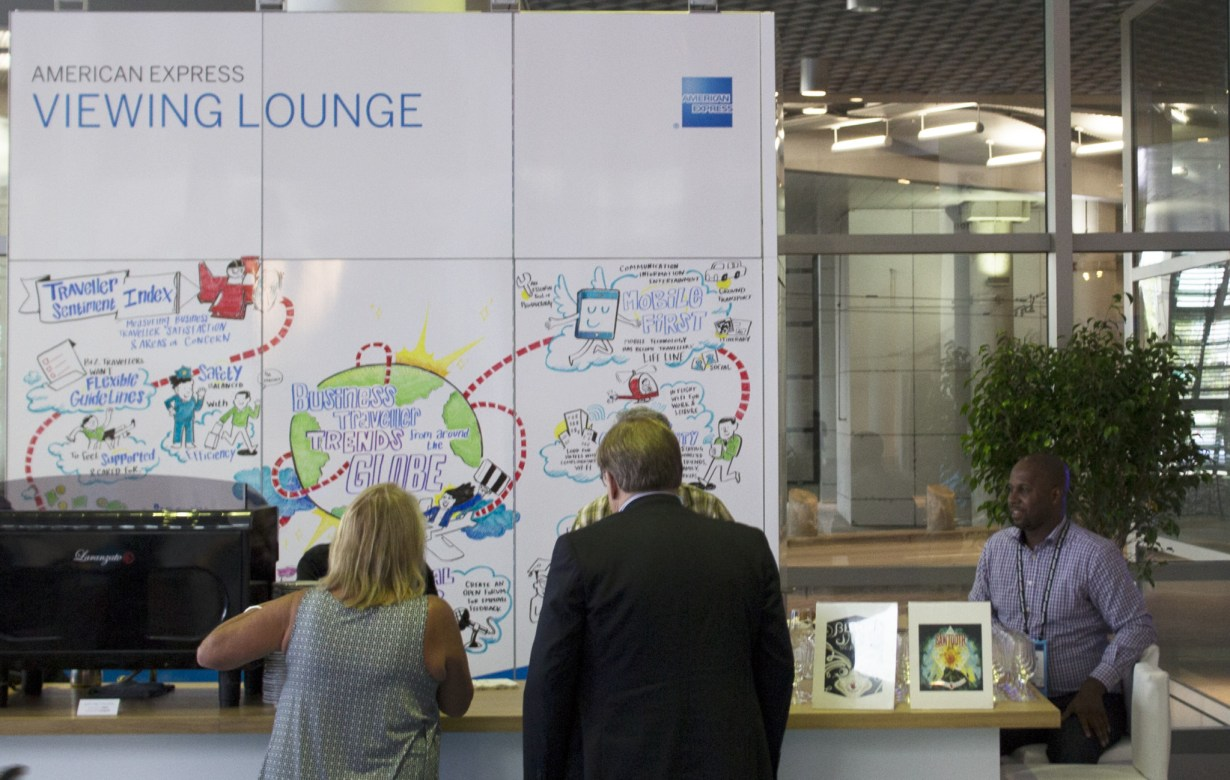 Two conference attendees look at imagethink infographic at amex lounge during global business travel association convention in Denver, CO, 2016.