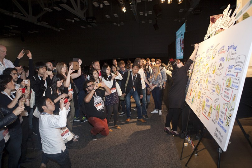 imagethink graphic recorder yao xiao completes a title at the top of a board at SXSWi while attendees photograph the content that was created during the session.