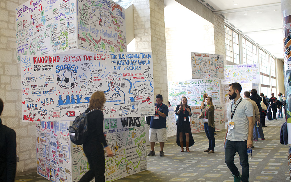 conference attendees walk around imagethink's graphic recording tower display at the 2015 sxsw conference in austin texas