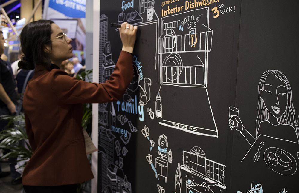 ImageThink graphic recorder Ona Rygelis scribes on a blackboard at a tradeshow booth.