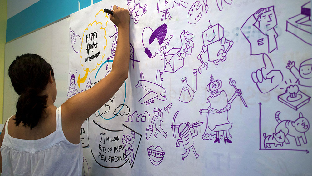 ImageThink graphic recorder Lilly Lam practices drawing icons at large scale.