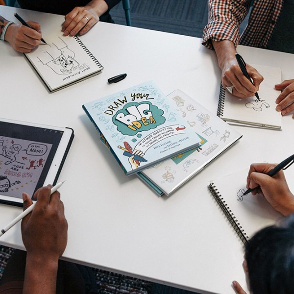 graphic recorders create sketchnotes at a desk with draw your big idea
