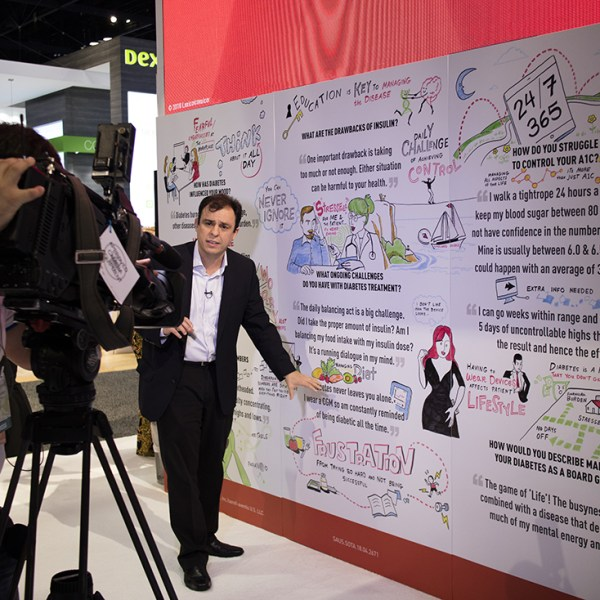 a camera man and reporter stand in front of an imagethink graphic recording at a healthcare tradeshow booth