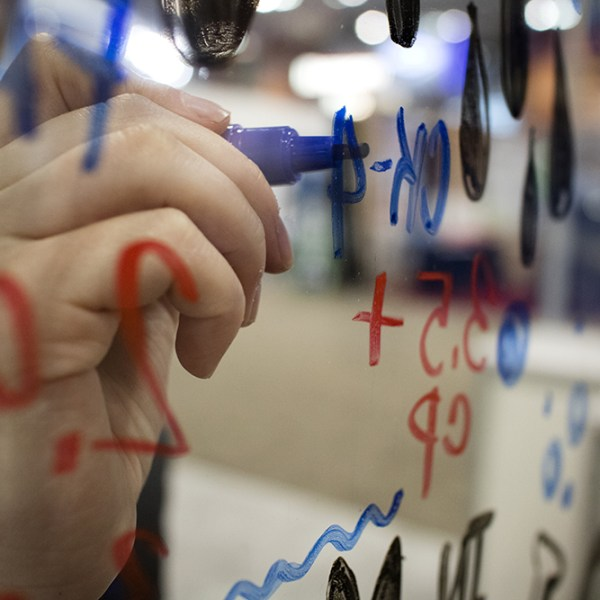 a graphic recorder from imagethink draws on a pane of glass to create an interactive conference experience