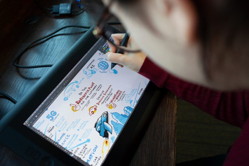 A graphic recorder working digitally in-studio on a client project using a Wacom Cintiq drawing tablet.