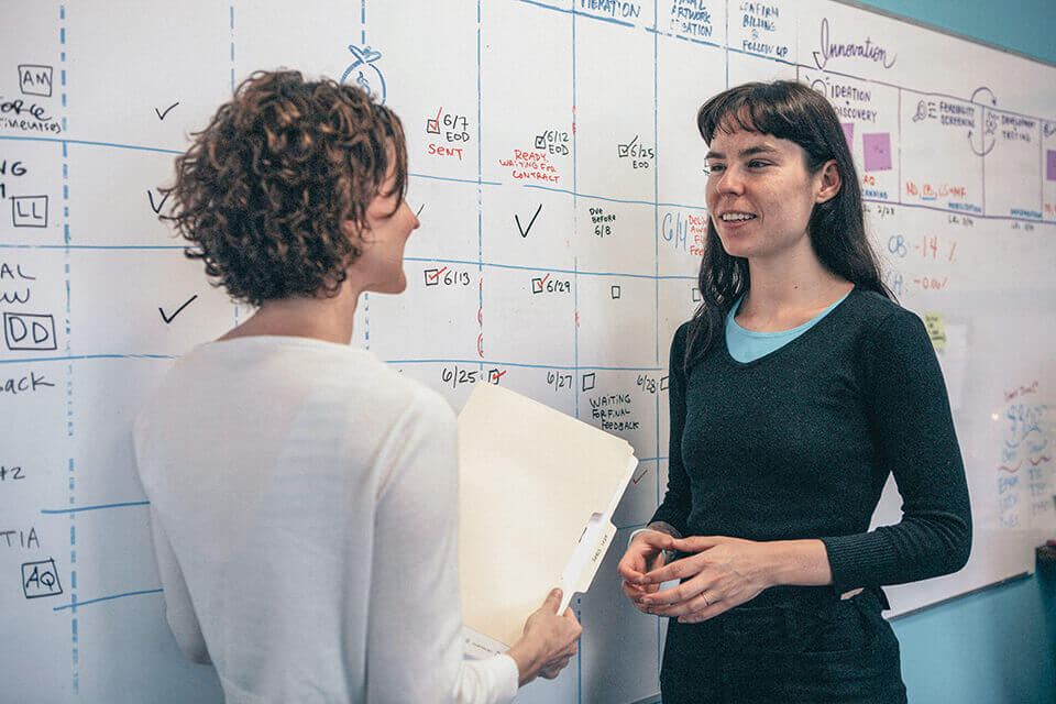 imagethink ceo nora herting and graphic recorder ona rygelis stand in front of a whiteboard calendar in their office