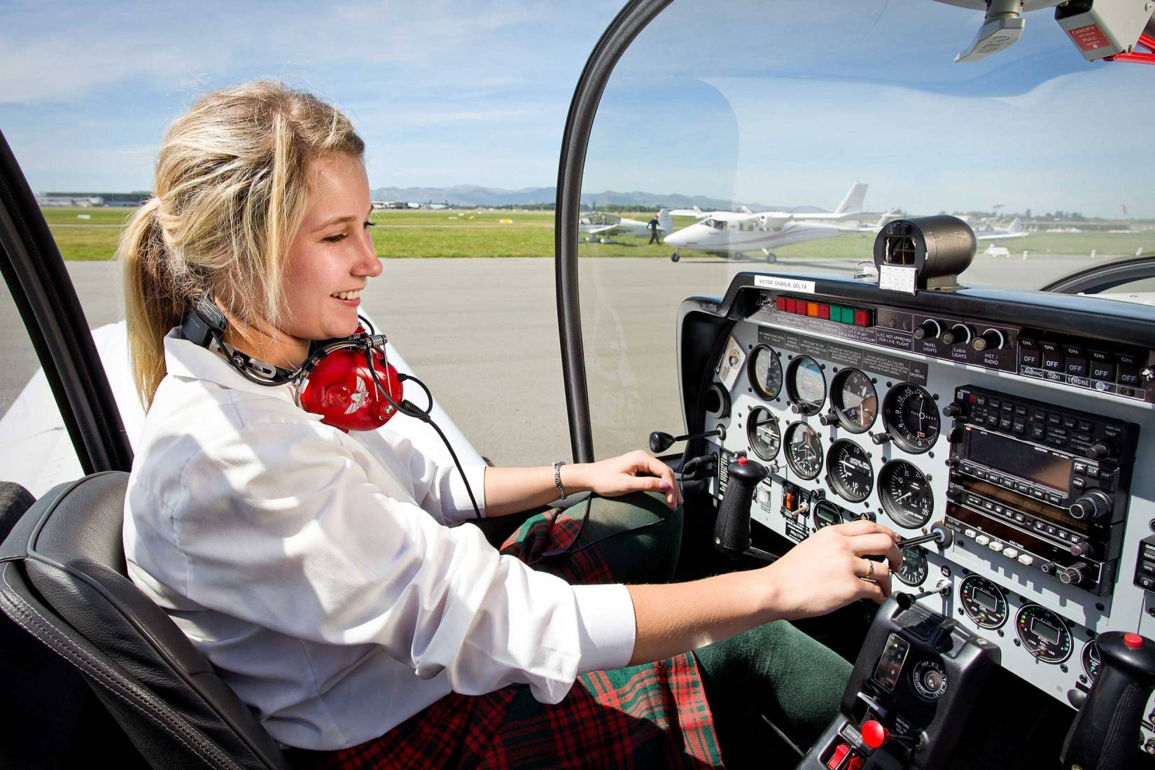 Commercial and editorial portrait of a young female pilot in the cockpit of a small plane.